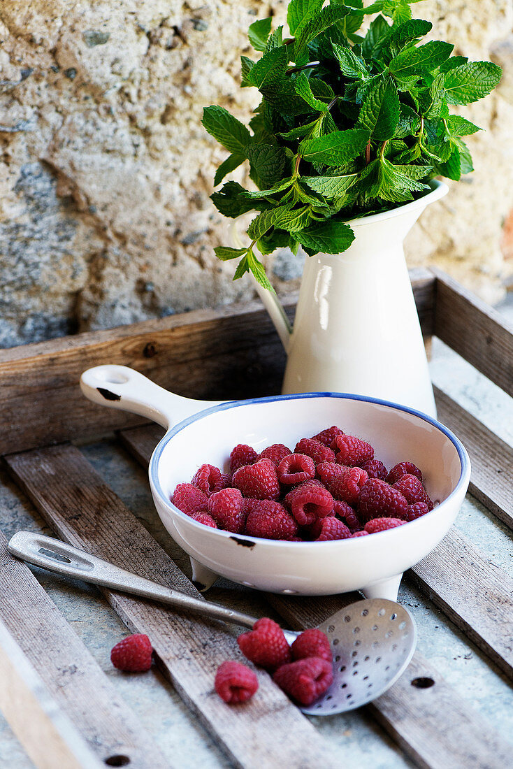 Raspberries in a ceramic bowl next to a jug of fresh mint