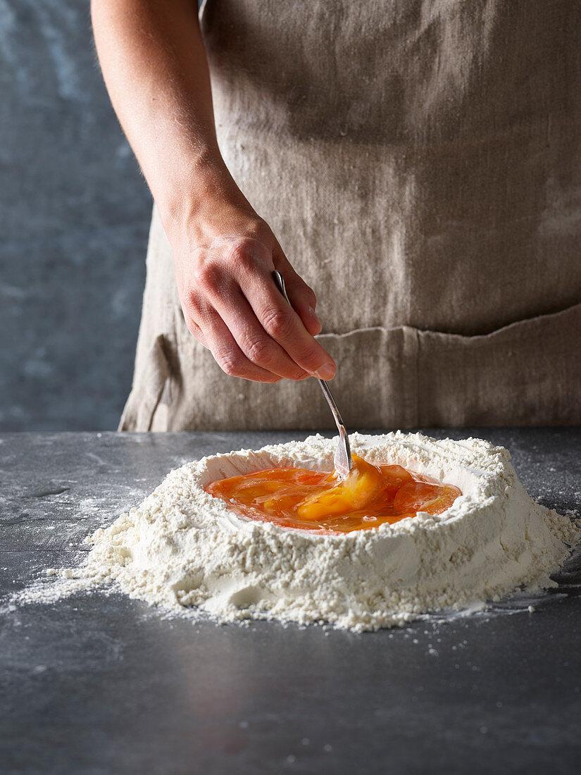 Nudelteig zubereiten: Rohe Eier in Mehlmulde vermischen