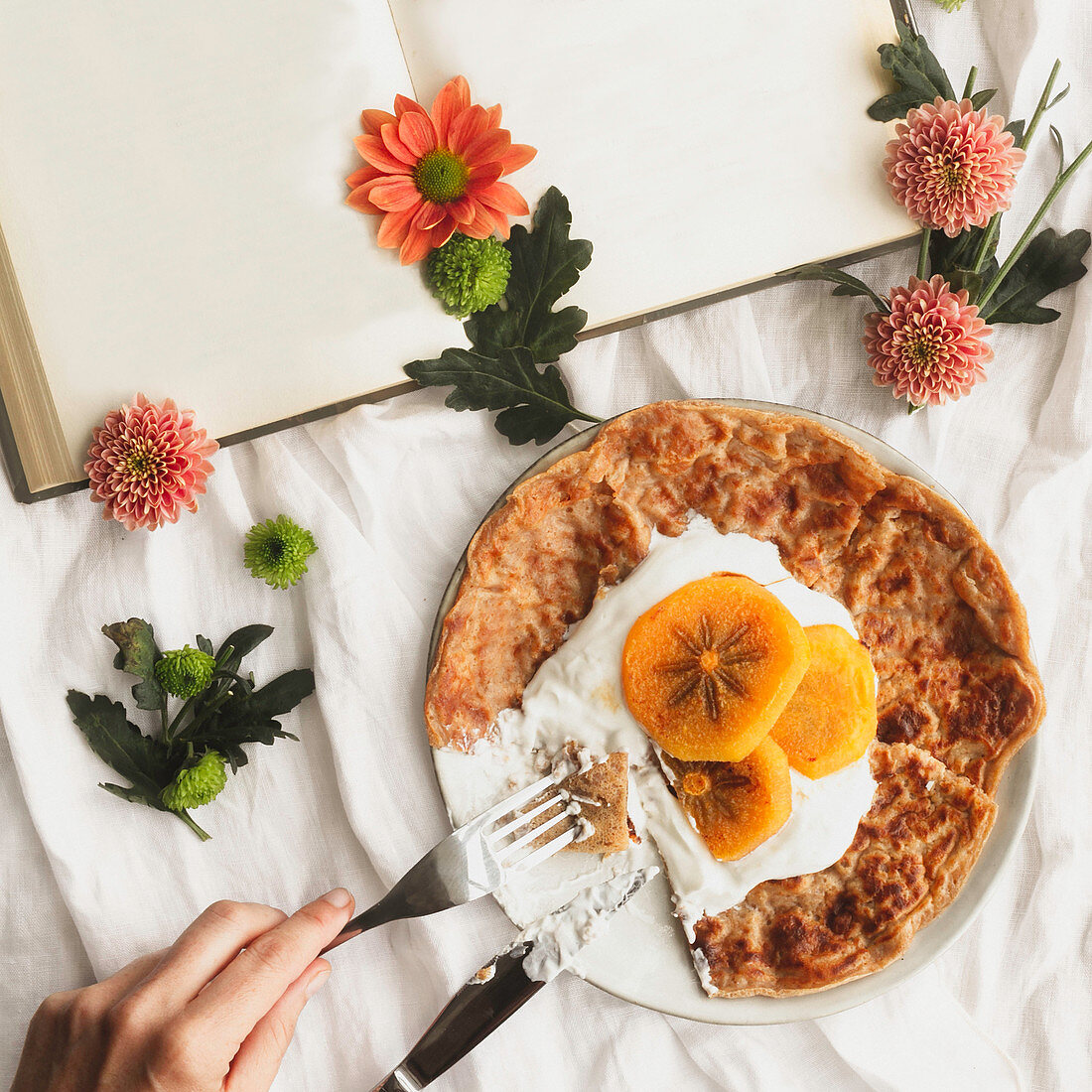 Homemade crepes with cream and sliced persimmon