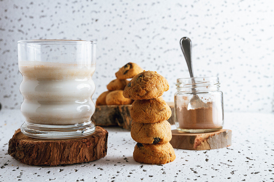Tasty brown cookies on wooden coasters standing on sackcloth and glass of dairy beverage