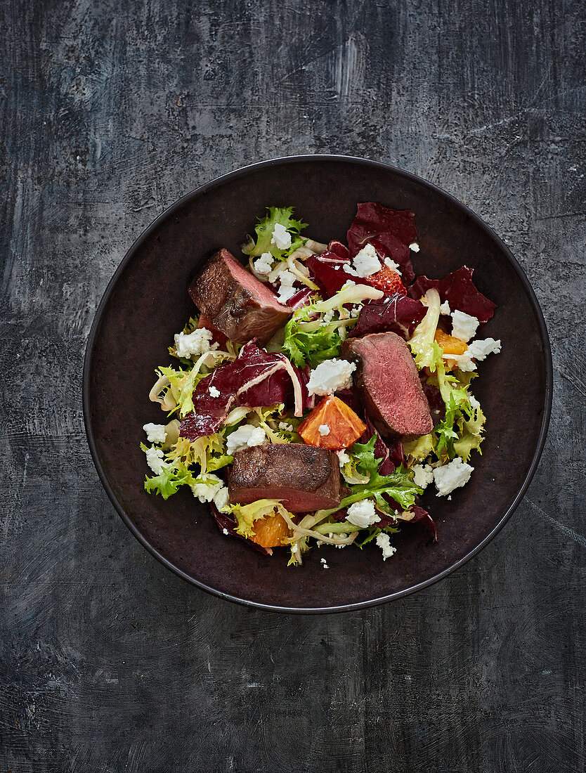 Seared saddle of venison with bitter lettuce leaves and an apple and mustard dressing