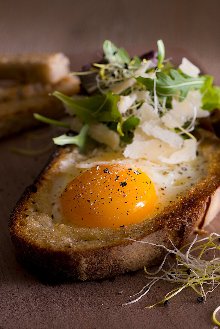 An egg baked into a slice of grilled bread with lettuce, beansprouts and Parmesan