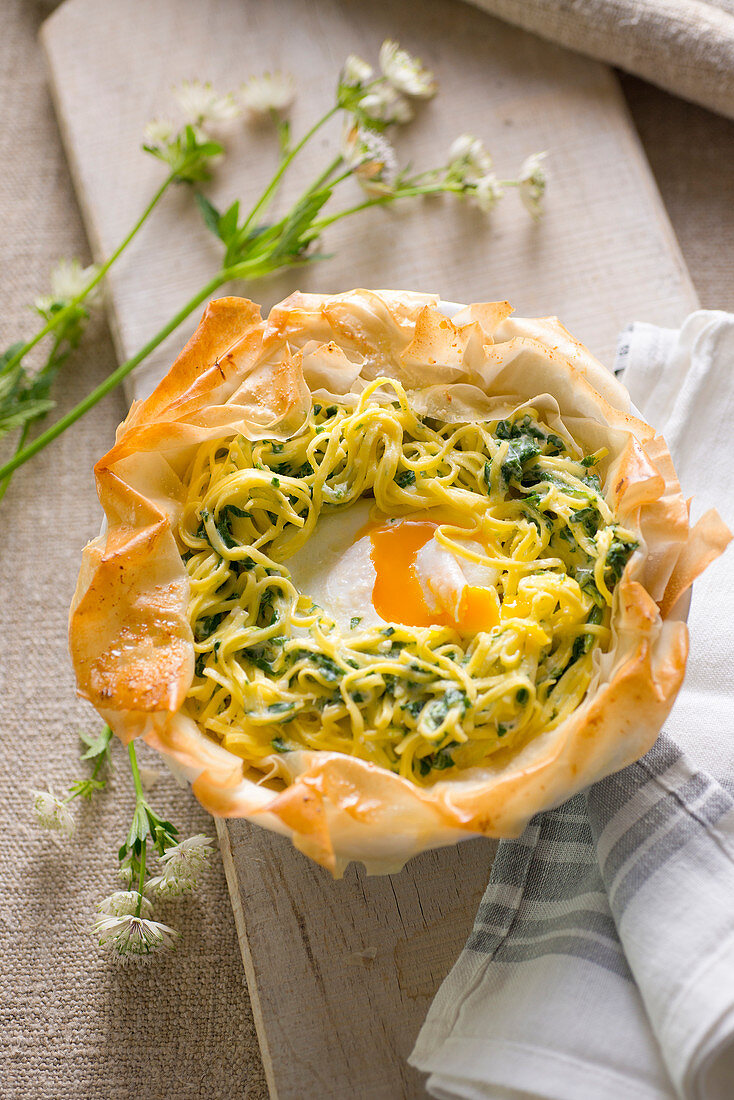 Chard noodles with a poached egg in a filo pastry basket