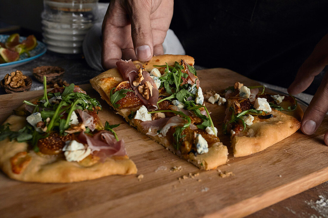 Taking piece of freshly made rustic pizza with figs, prosciutto and goat cheese