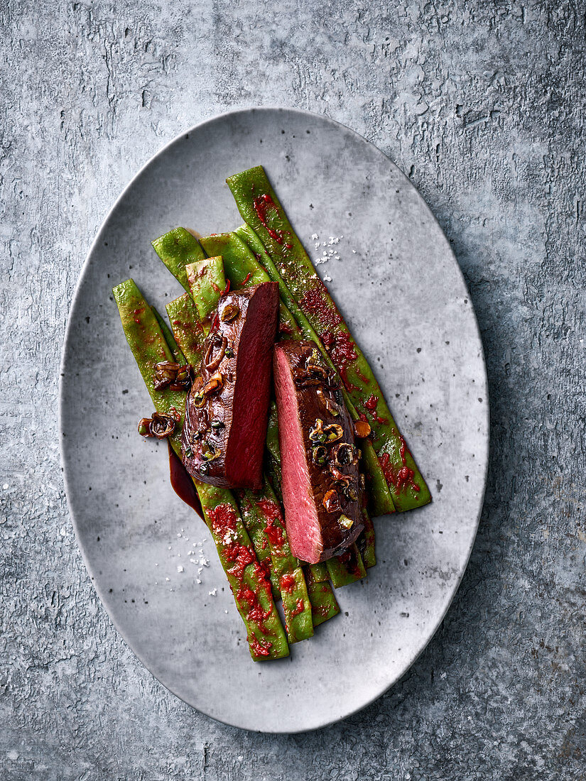 Oriental saddle of venison with a bean medley