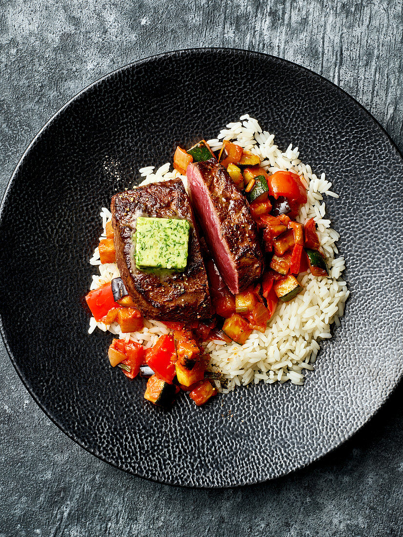 Fried vegetables with venison steaks and rice