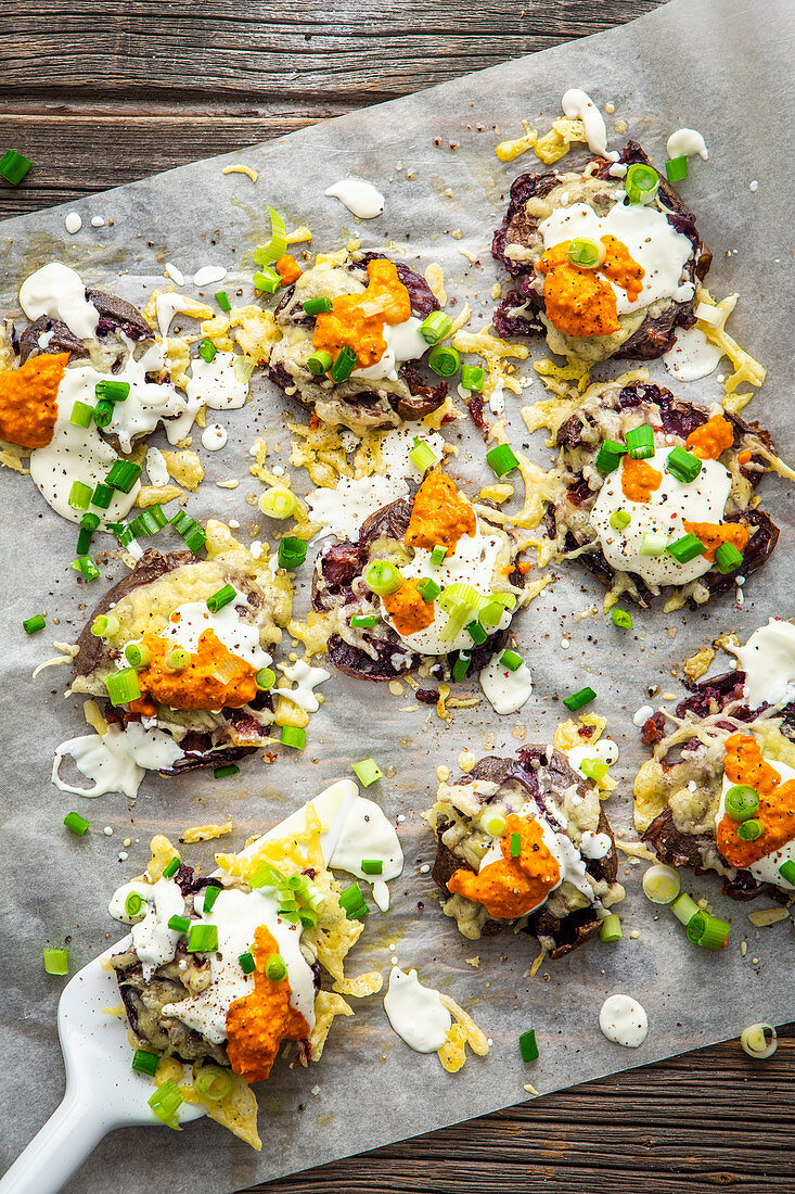 Squashed purple potatoes with cheese, sour cream and pesto