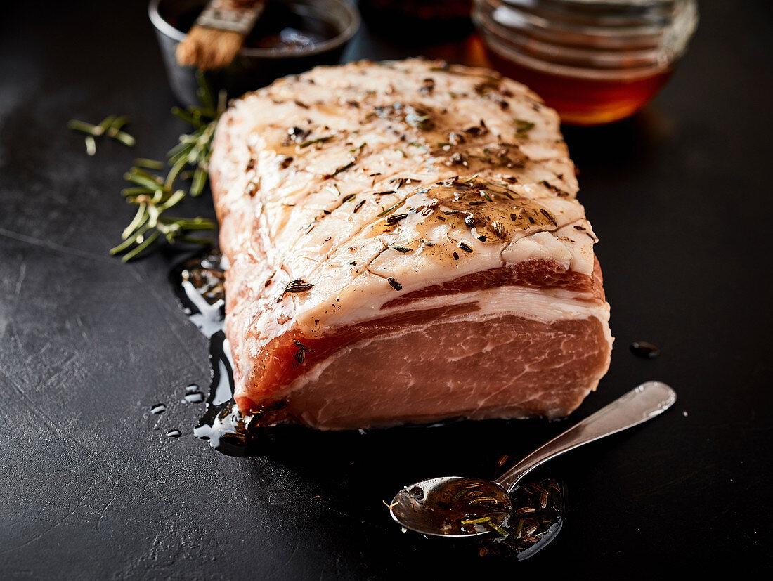 Raw pork collar roast marinated with honey, allspice and fennel