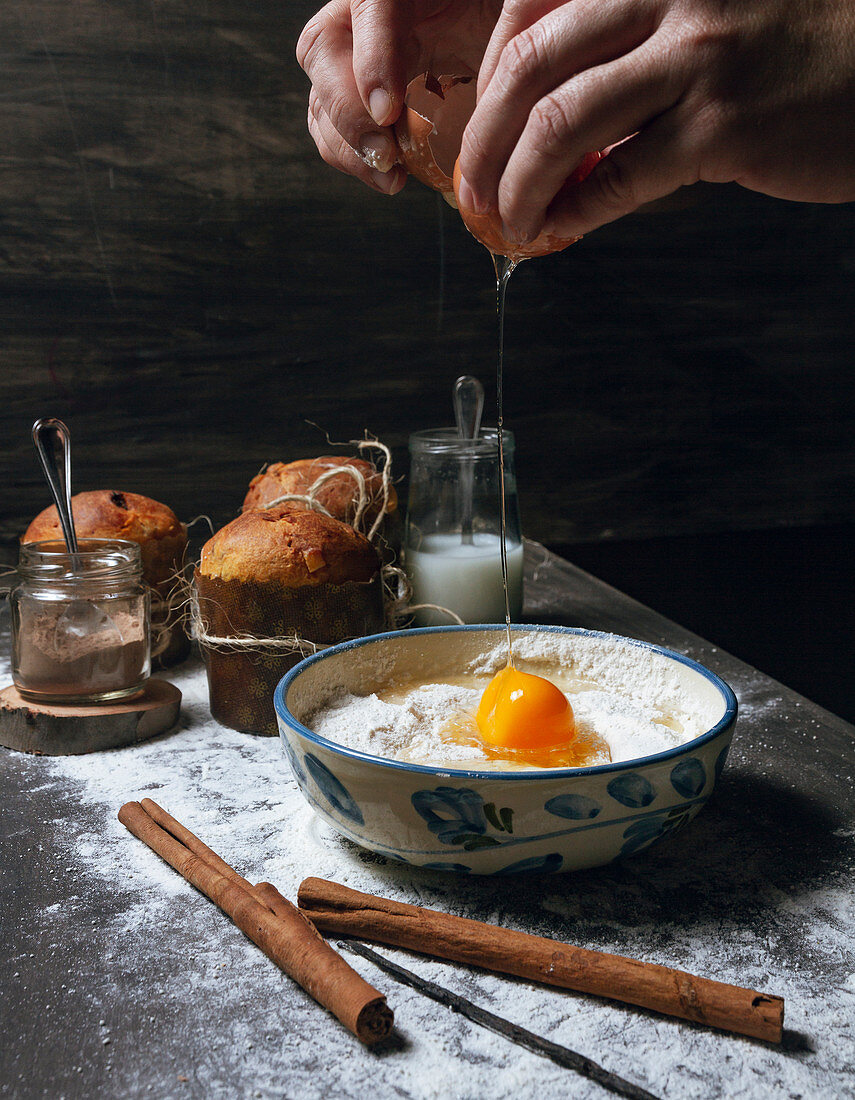 Person breaking egg into ceramic bowl - baking ingredients for a dough