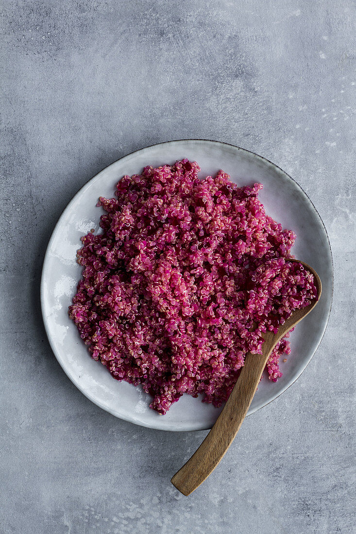 Rotes Quinoa mit Holzlöffel auf Teller