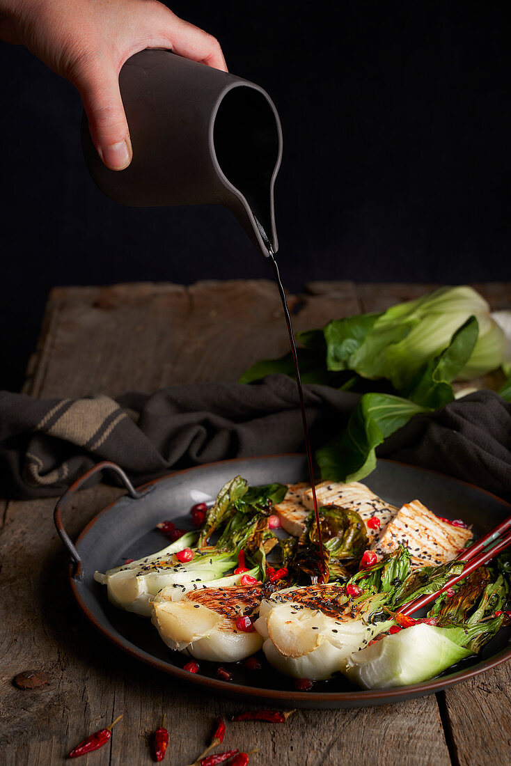 Person spilling soy sauce from jug on bok choy salad with fish