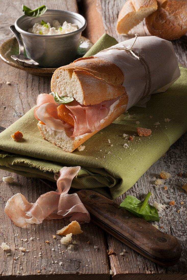 A baguette sandwich with Parma ham, spinach and cream cheese