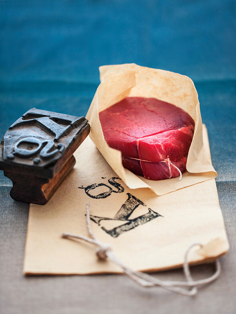 Still life with a beef medallion and a stamp