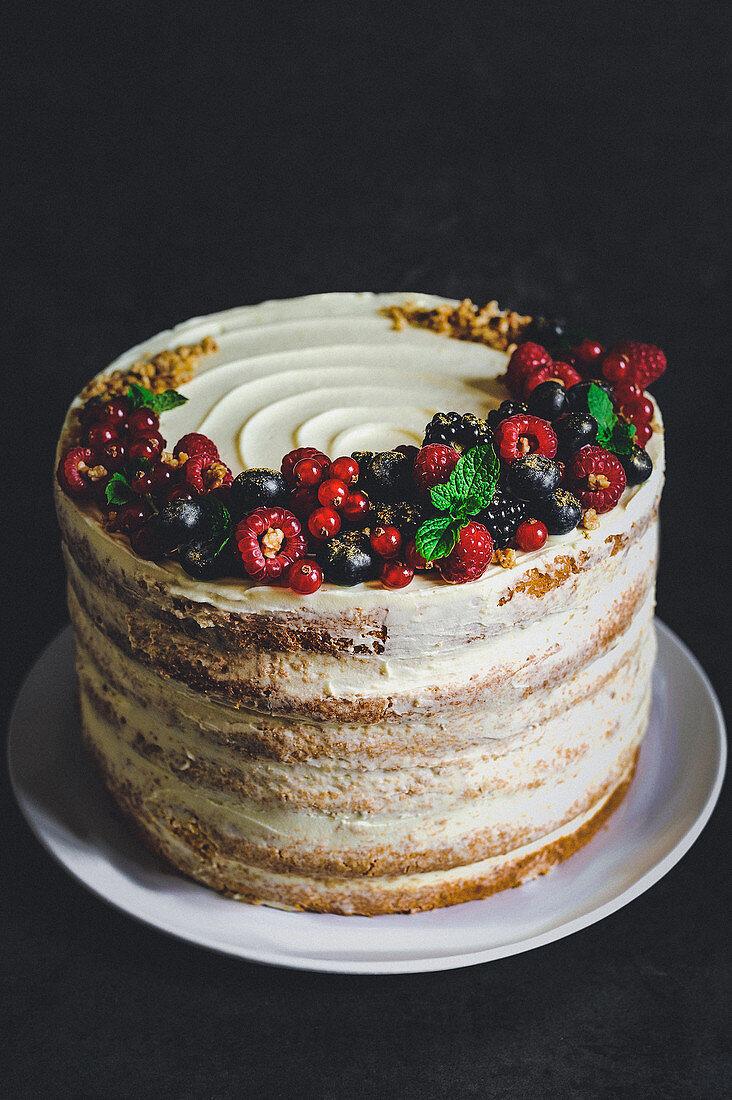 Vanilla sponge cake with cream cheese frosting, berries, gold powder and hazelnut brittle