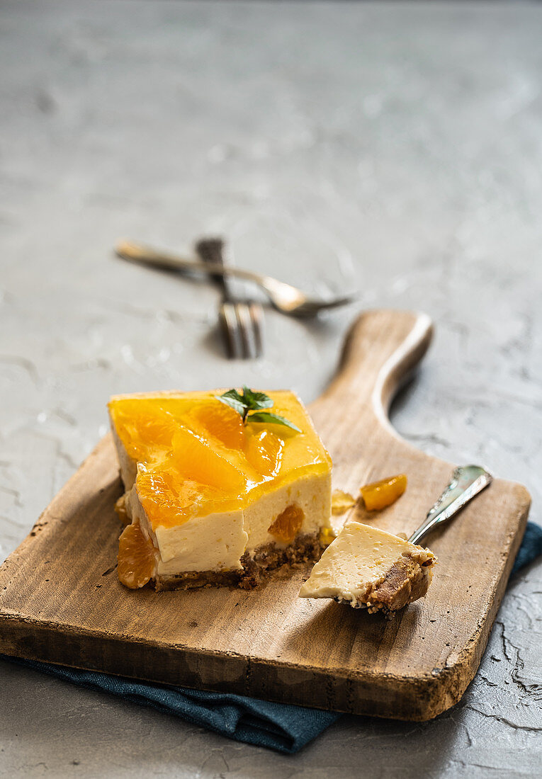 A piece of cheesecake with mandarins on a wooden board