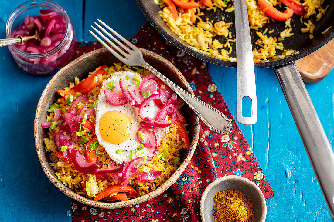 Fried curry rice with veggies, fried egg and caramelized onion