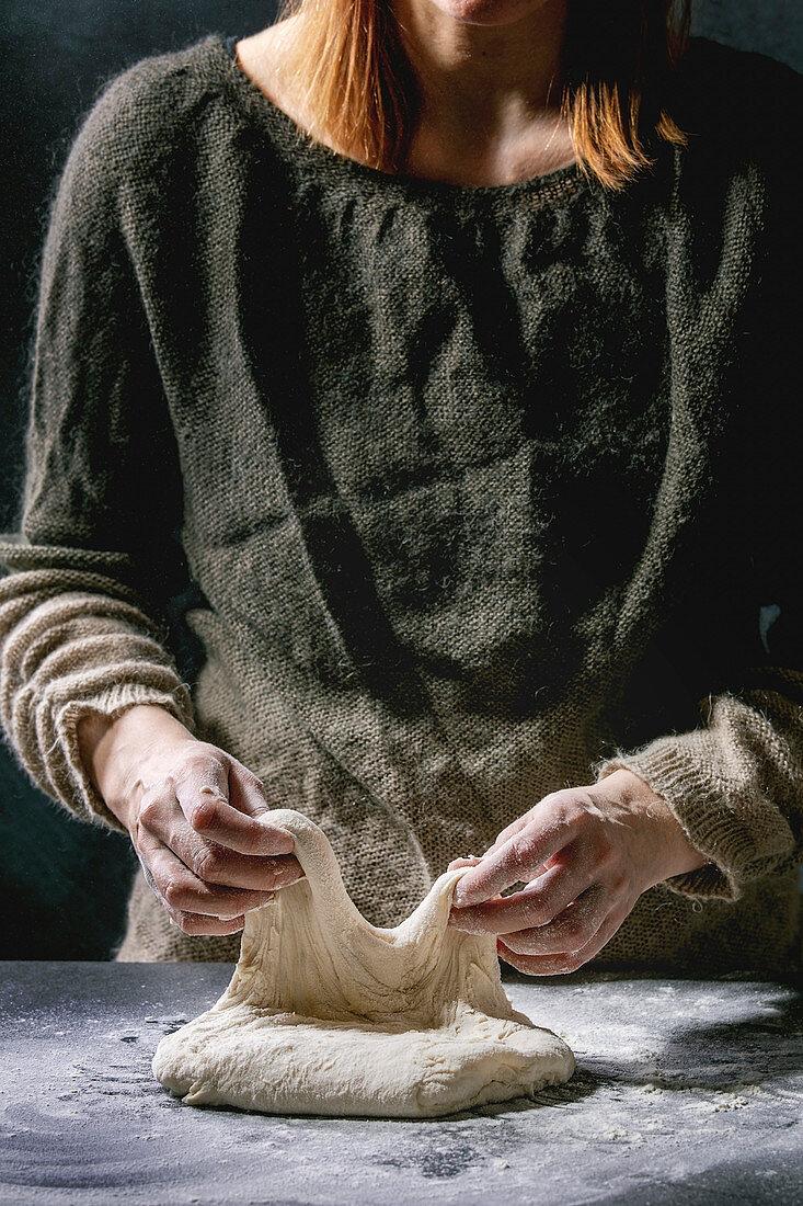 Process of making homemade bread dough: Female hands kneading dough
