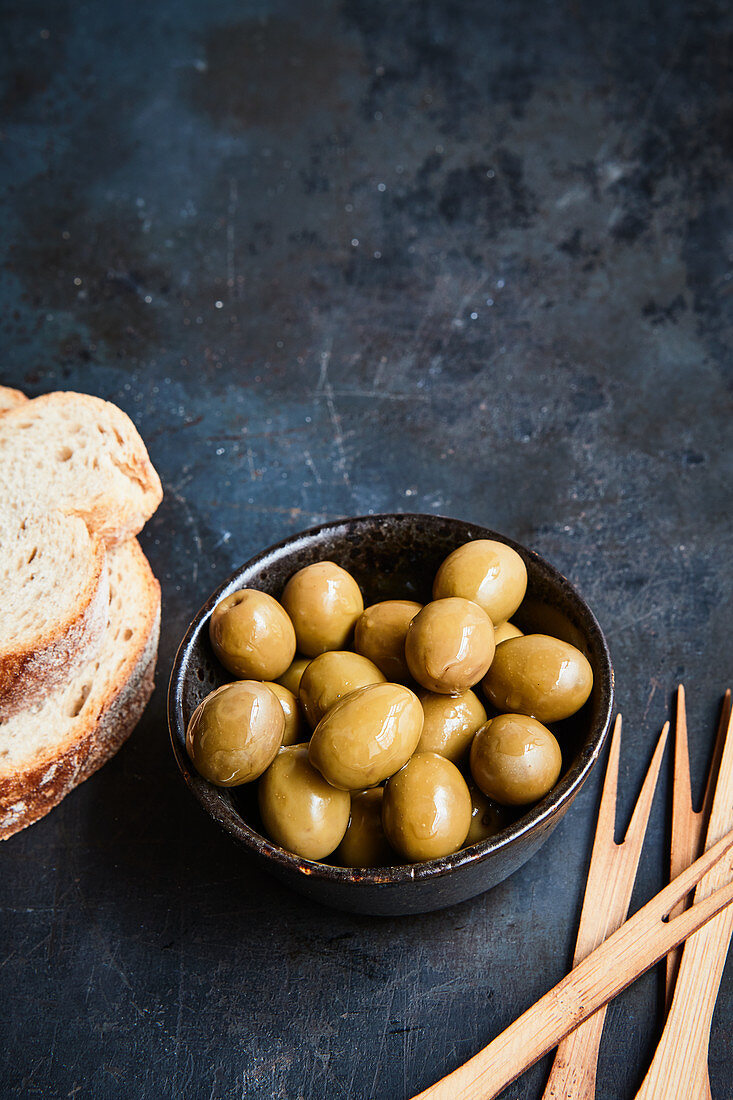 Green olives, white bread and skewers