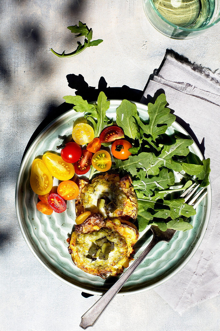 Roasted Poblano Pesto Smashed Potatoes served on a bed of arugula and cherry tomatoes