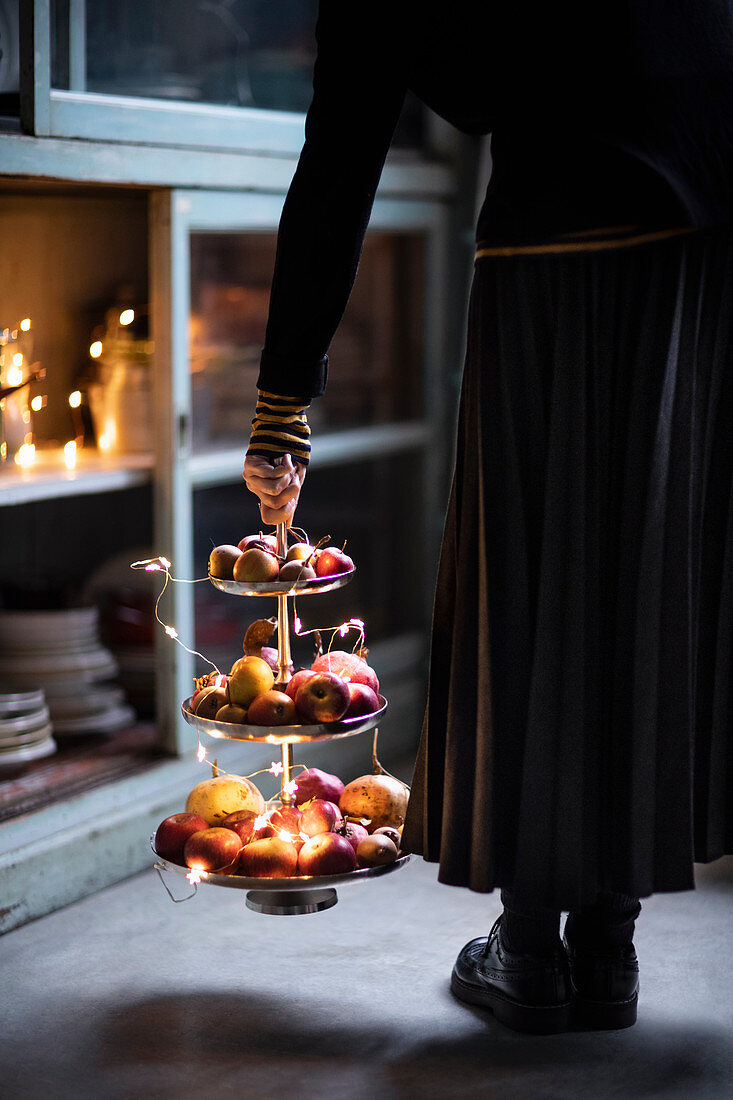 A woman with a bright fruit cake stand