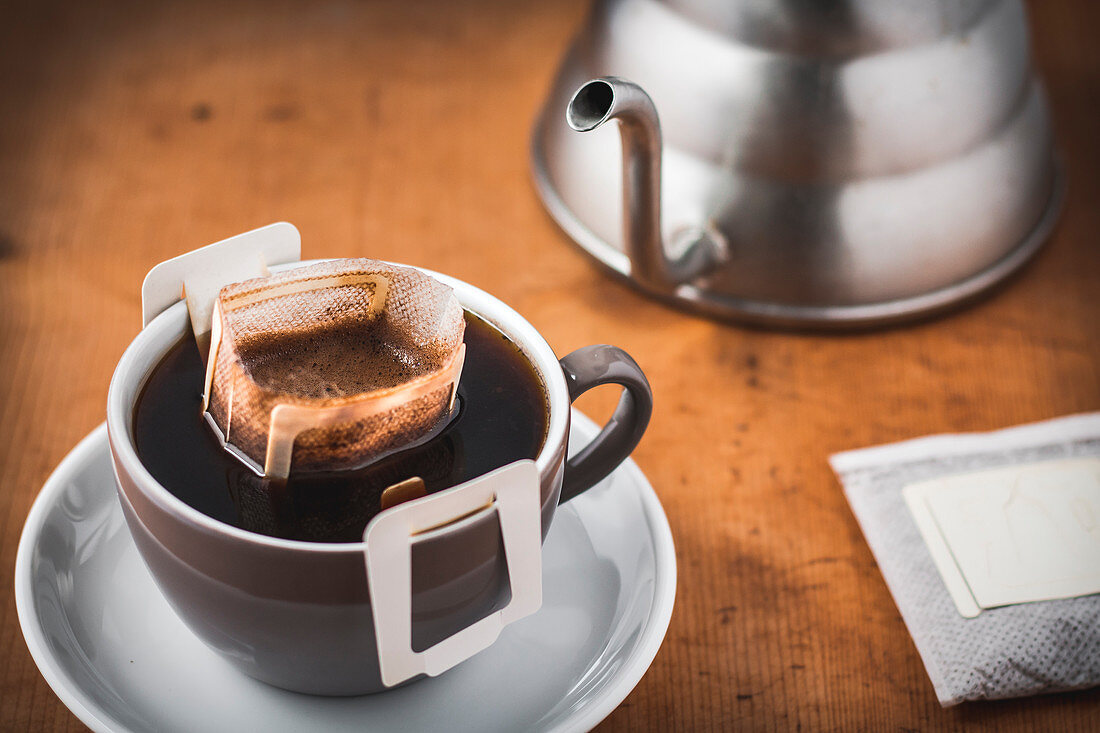 Ready brewed coffee with a coffee drip bag in a coffee cup