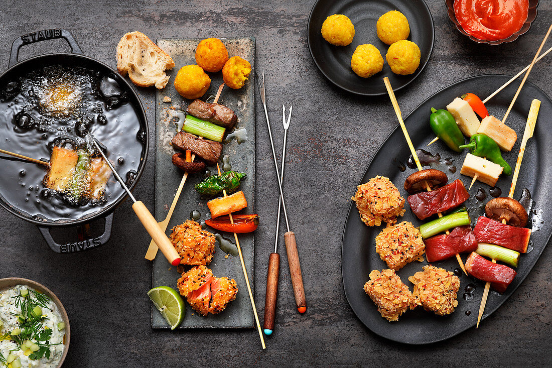 Fondue with oil: beef skewers, salmon bites, pepper and cheese skewers