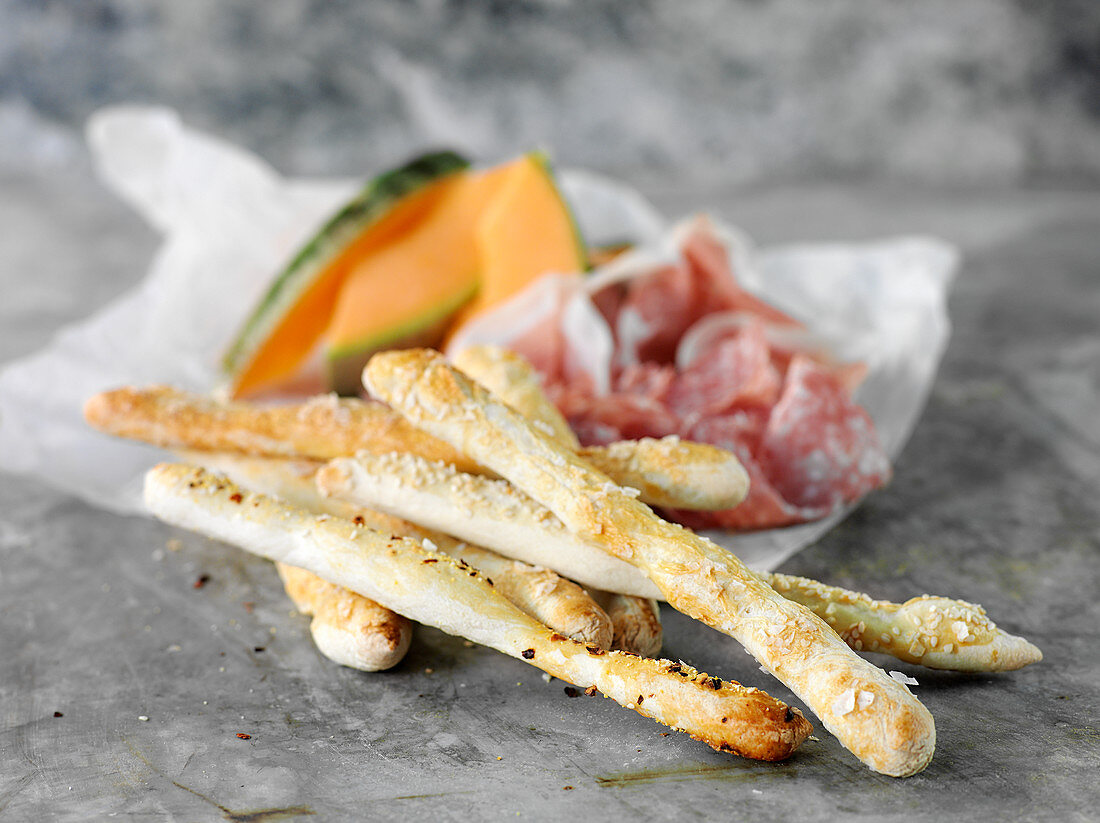 Homemade grissini with parma ham and melon