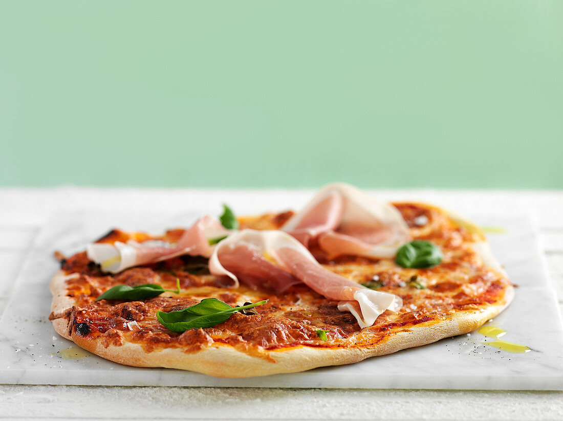 Pizza with parma ham and basil