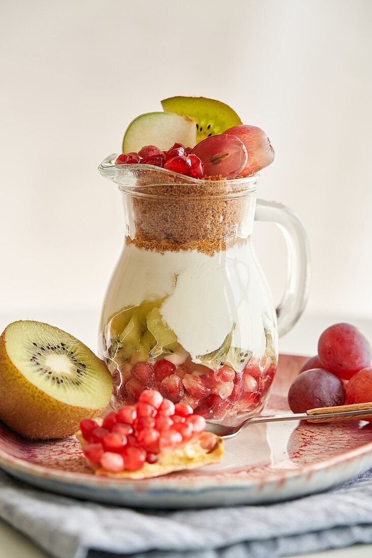 Delicious yogurt dessert with pomegranate, kiwi, grape and ginger biscuit