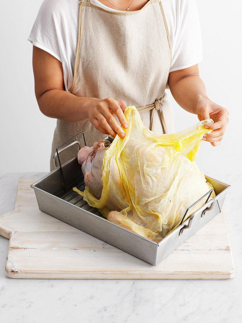 Whole roast turkey preparation: drape the buttered muslin over