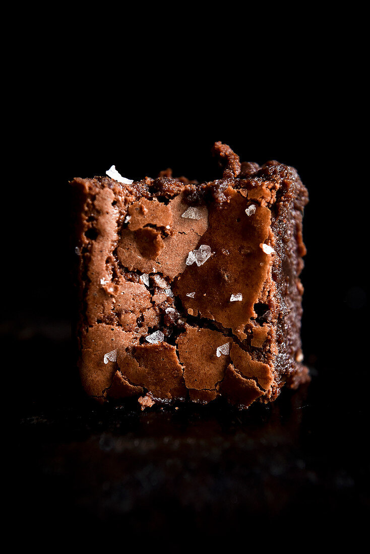 A brownie with flakes of sea salt against a black background