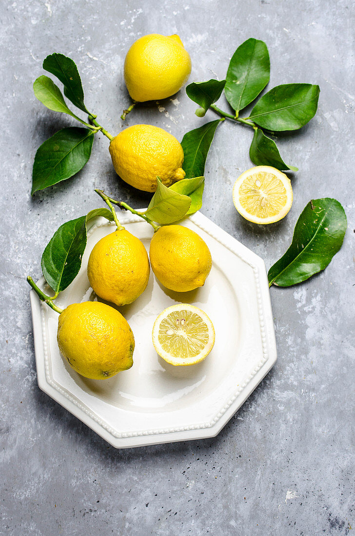 Lemons, halved and whole with leaves