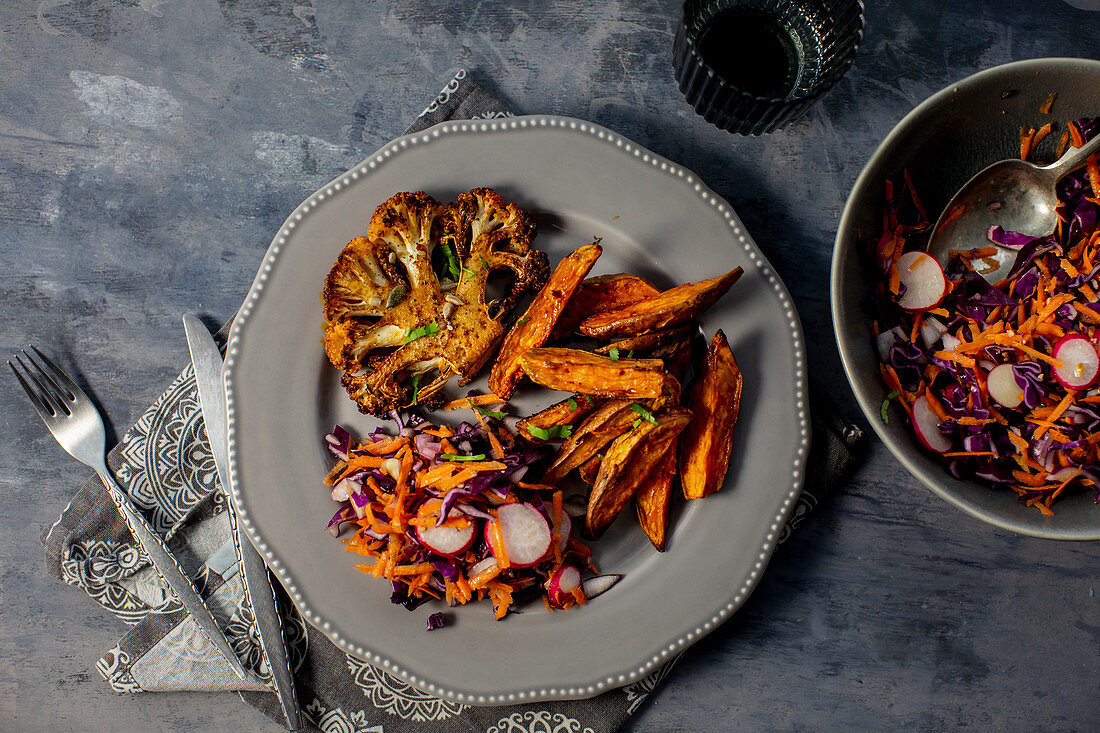 Spicy cauliflower 'steak' with red cabbage salad and sweet potato fries