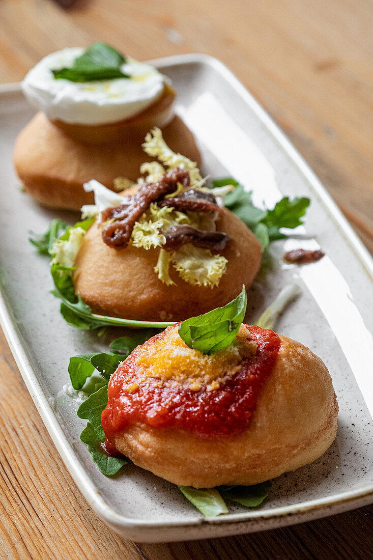 Deep fried buns garnished with sauce and vegetables and served on plate with fresh greenery in cafe