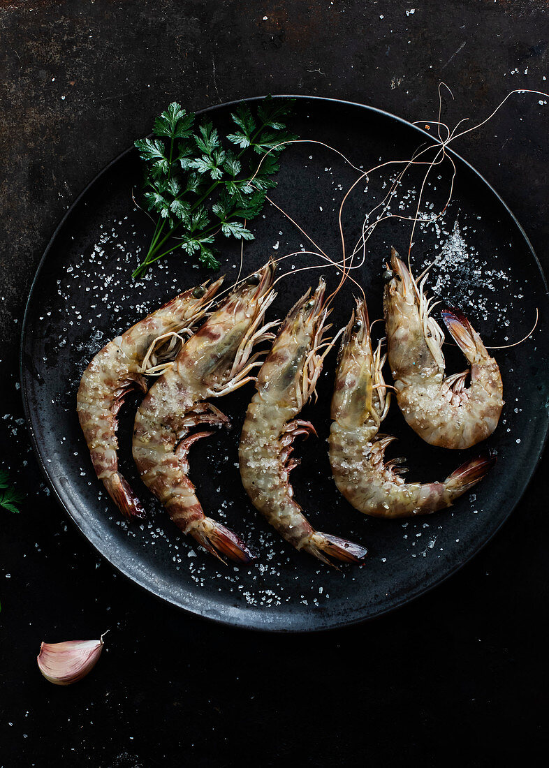 Prawns served in plate on table on dark background