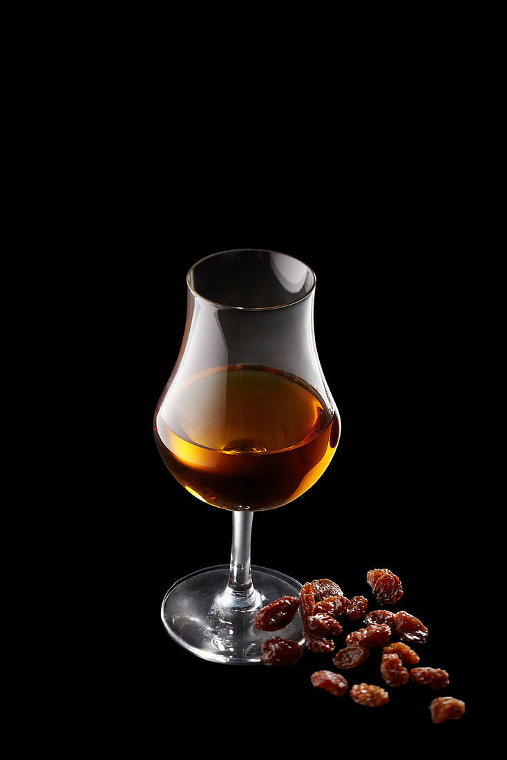 A glass of rum with a pile of raisins