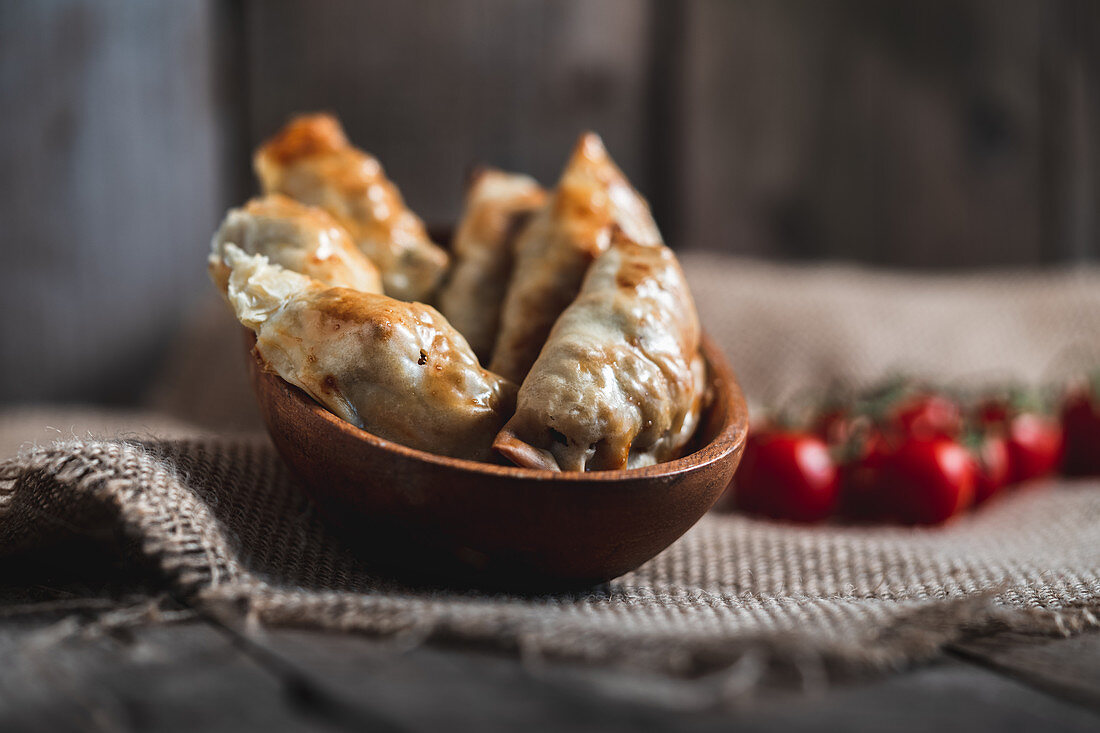 Traditional Spanish homemade turnovers served in bowl on rustic wooden table with tomatoes