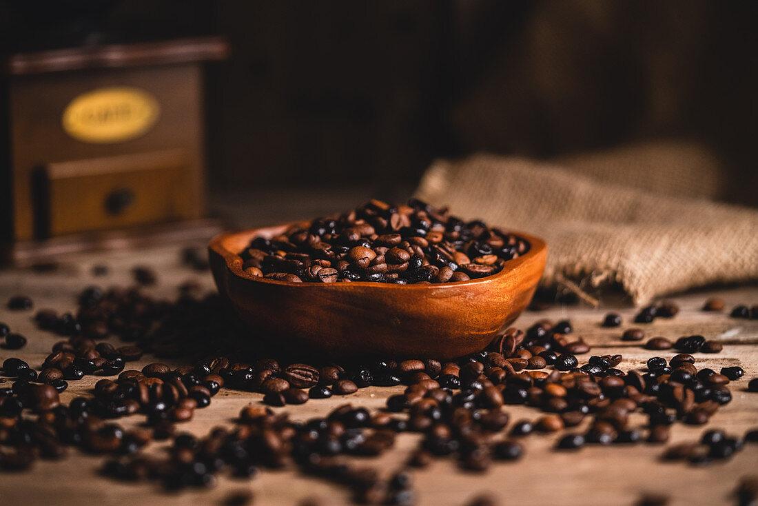 Kaffeebohnen in Holzschale vor einer Vintage-Kaffeemühle