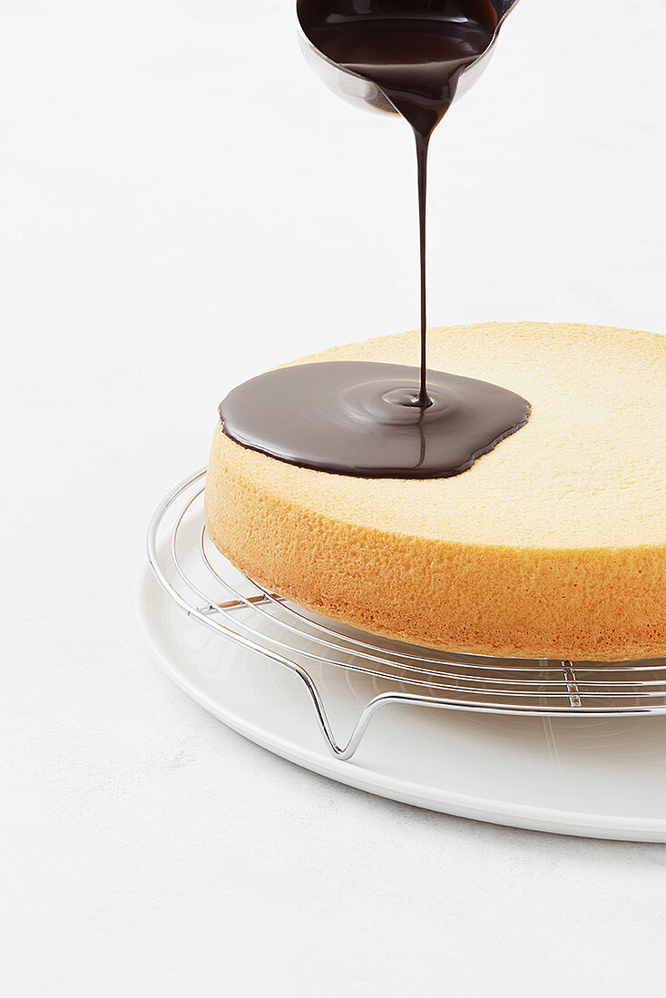 A cake being covered with a chocolate glaze