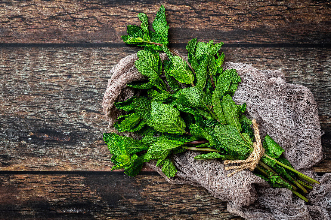 Bunch of fresh green aromatic mint twigs arranged on rustic wooden table