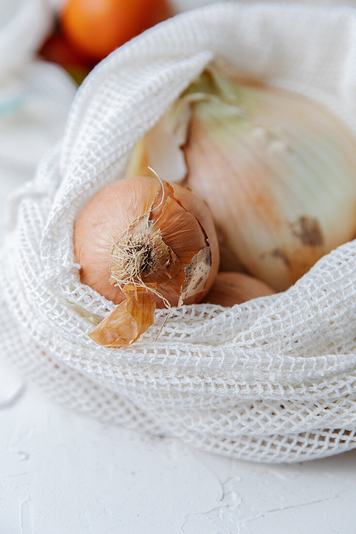 Fresh onions in eco friendly textile bags placed on table in kitchen