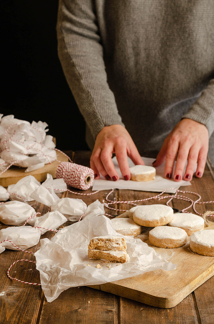 Hand wrapping tasty homemade Polvorones in paper while preparing gifts for Christmas celebration