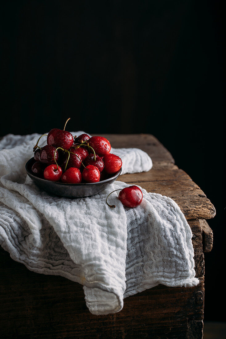 Bow full of fresh cherries on wooden table and white muslin fabric against dark background