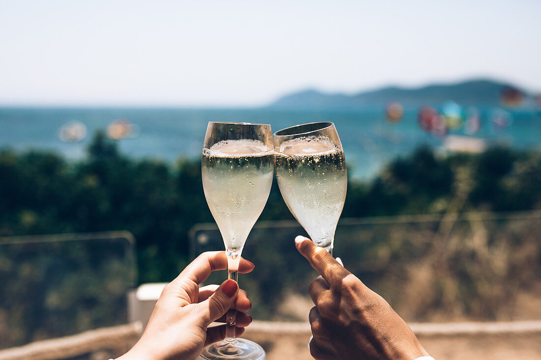 Crop anonymous couple enjoying summer holidays and cheering with glasses of champagne while spending sunny day at seaside