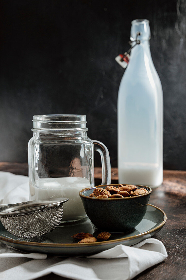 Jar and bottle of vegan milk and bowl of almonds placed on rustic table near napkin and strainer