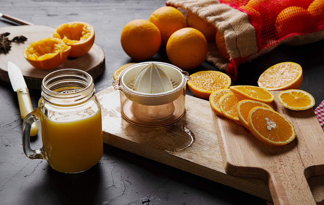 Halves of fresh oranges on wooden boards and mesh bag near glass jar with orange custard