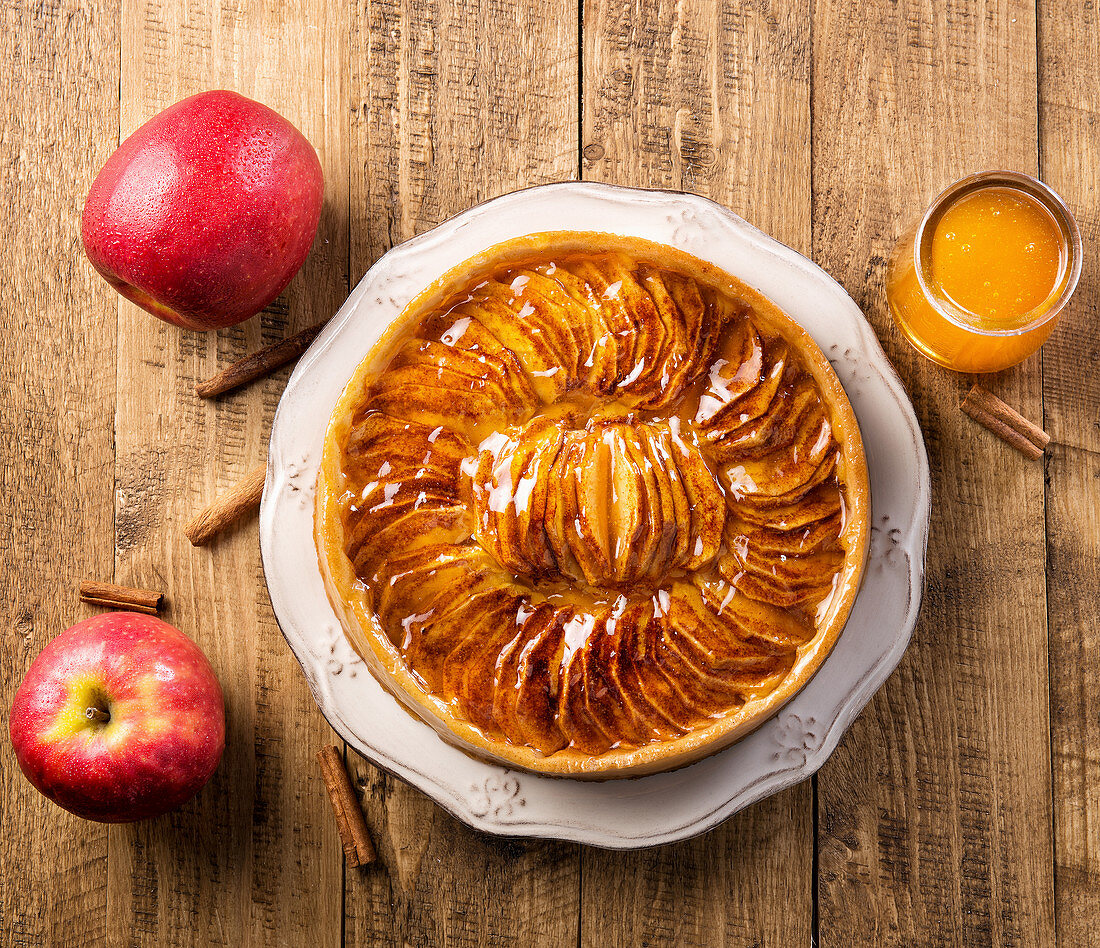 Top view served whole pie with apples in syrup placed on plate among fresh apples on wooden table