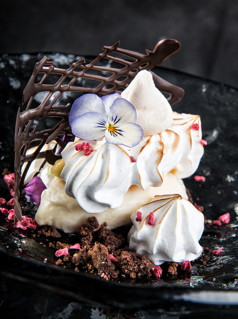 Dessert made from meringue cookies decorated with violet flower and placed on plate with cream and chocolate