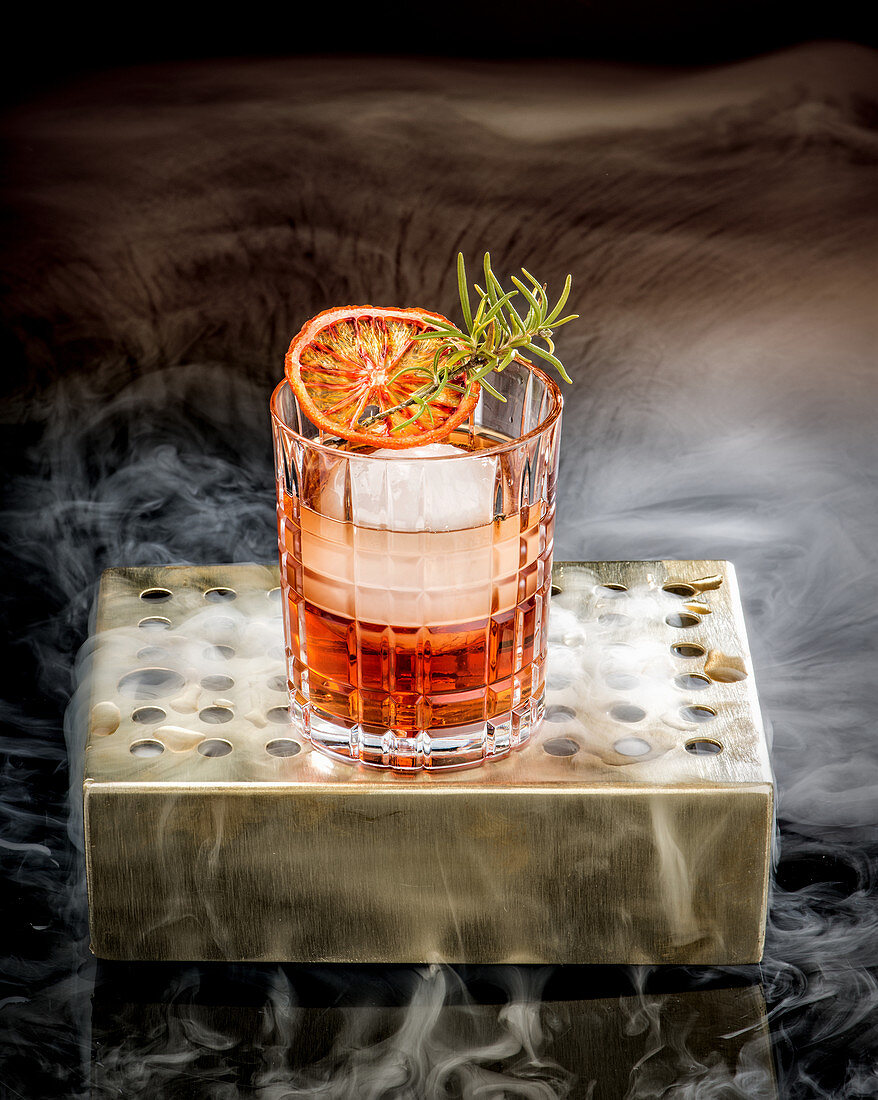 Alkoholischer Cocktail mit Blutorange, Eiswürfeln und Rosmarin