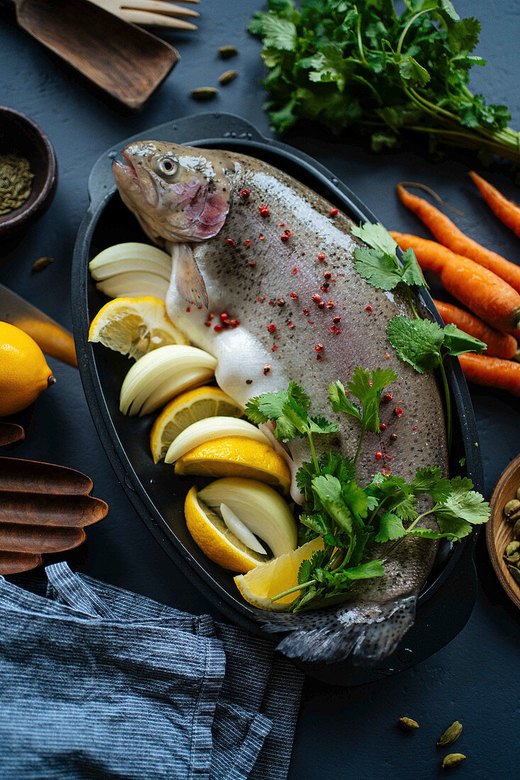 Fresh trout with lemon and onions for preparation in kitchen